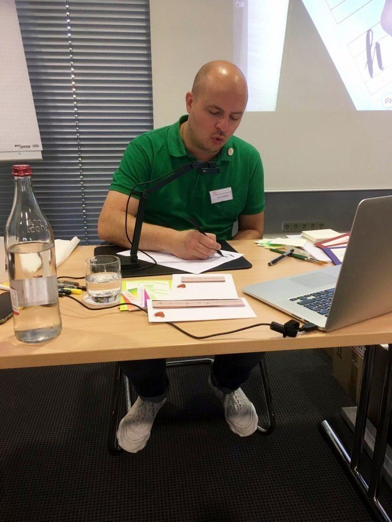 Marcel Warnt zeigt in der Schulung auf der 20. Generalversammlung das Handlettering.