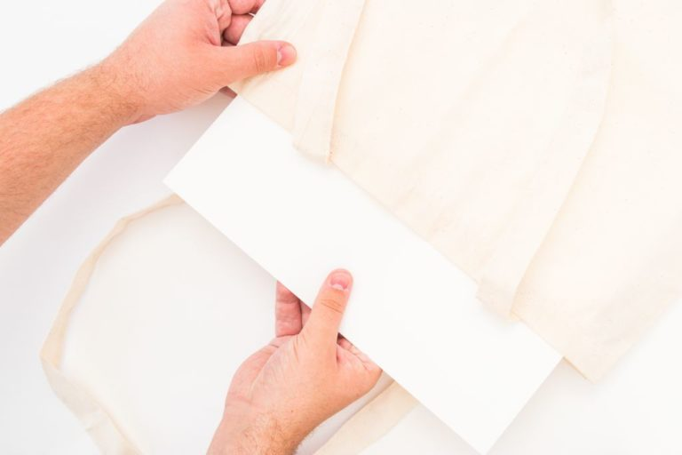 Pappe wird in die Tasche gelegt.