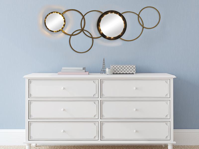 Eine weiße Kommode mit einem Wandbild aus Holzringen und Spiegeln.