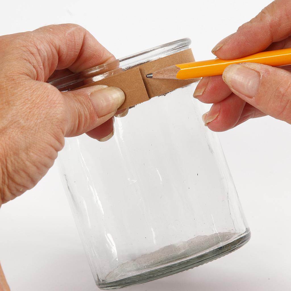 Ein Streifen Kunstlederpapier wird am Glas von der Länge her angeoasst.