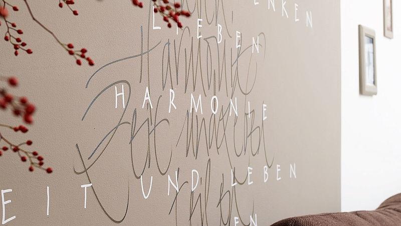 Eine Wand mit einem Zitat in grauer und weißer Schrift.