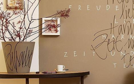 Eine beschrifteter Übertopf passend zur Wandgestaltung.