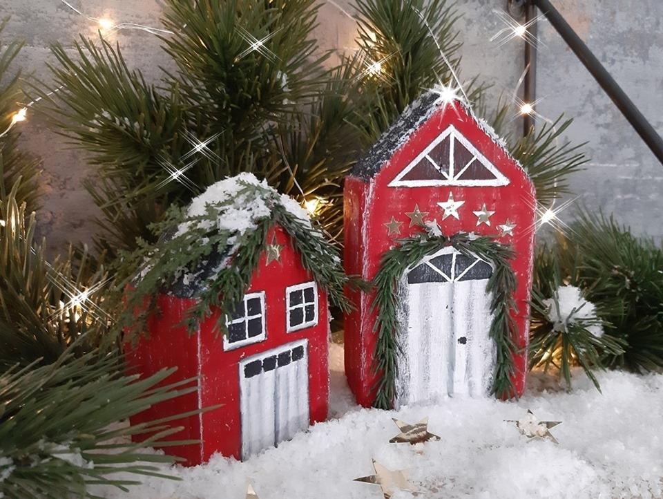 2 Holz Häuser weihnachtlich bemalt stehen auf einem Regal.