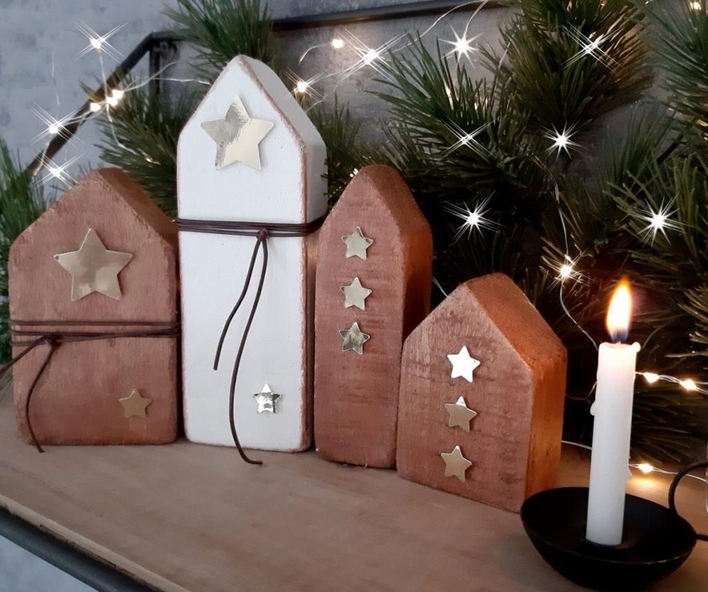 4 kleine Holz Häuser stehen auf einem Regal