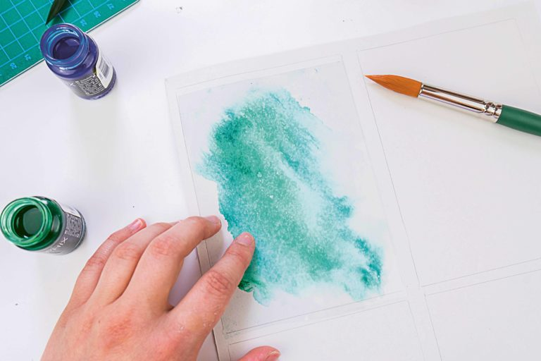 Aquarellfarbe wird mittels einer Fensterfolie verstrichen.