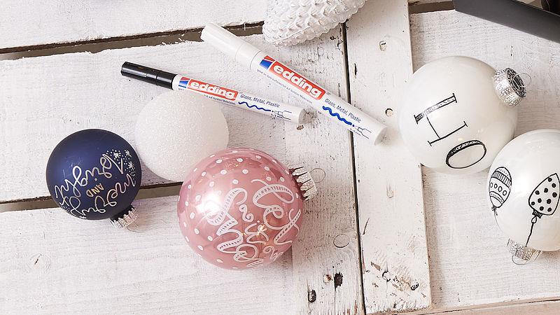 Weihnachtskugeln werden mit Lackmalstiften bemalt.