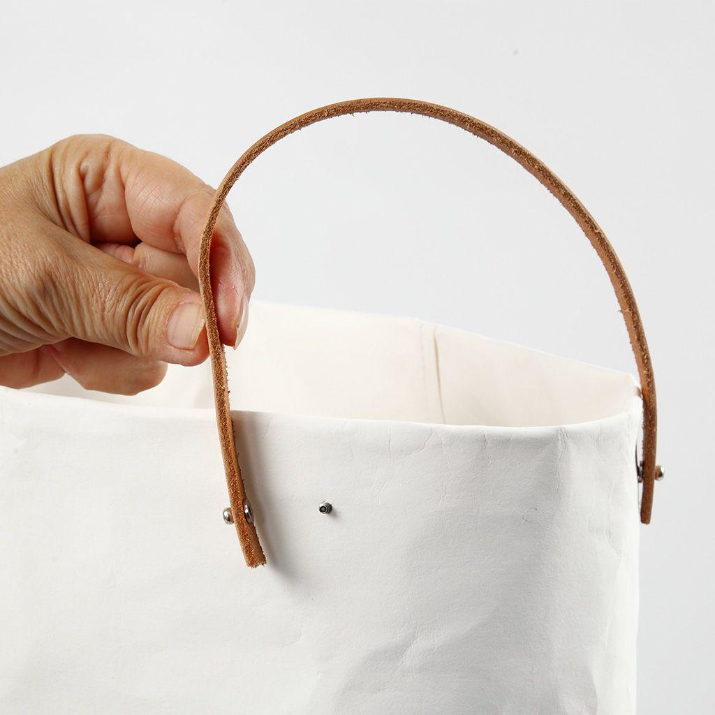 Der Henkel wird mit Nieten an den Behälter zur Aufbewahrung von Geschenkpapier angebracht.