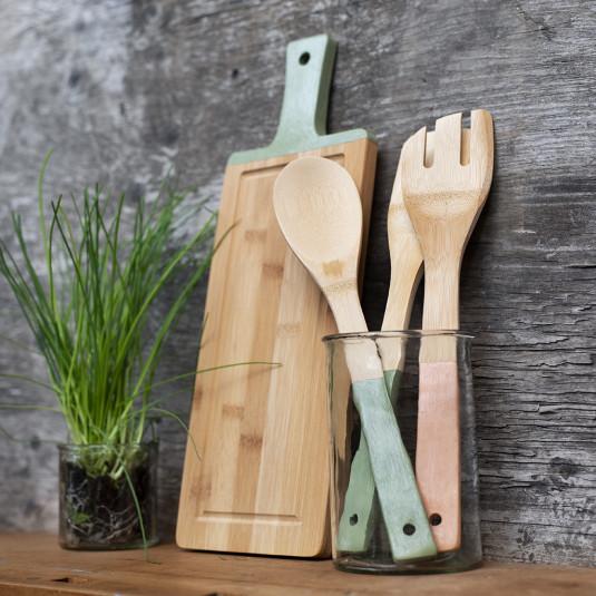 Ein Gefäß mit Kochlöffeln und ein Schneidebrett aus Bambus.
