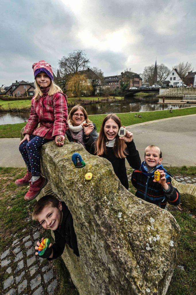 Eine Familie in Goch vor einem großen Stein.