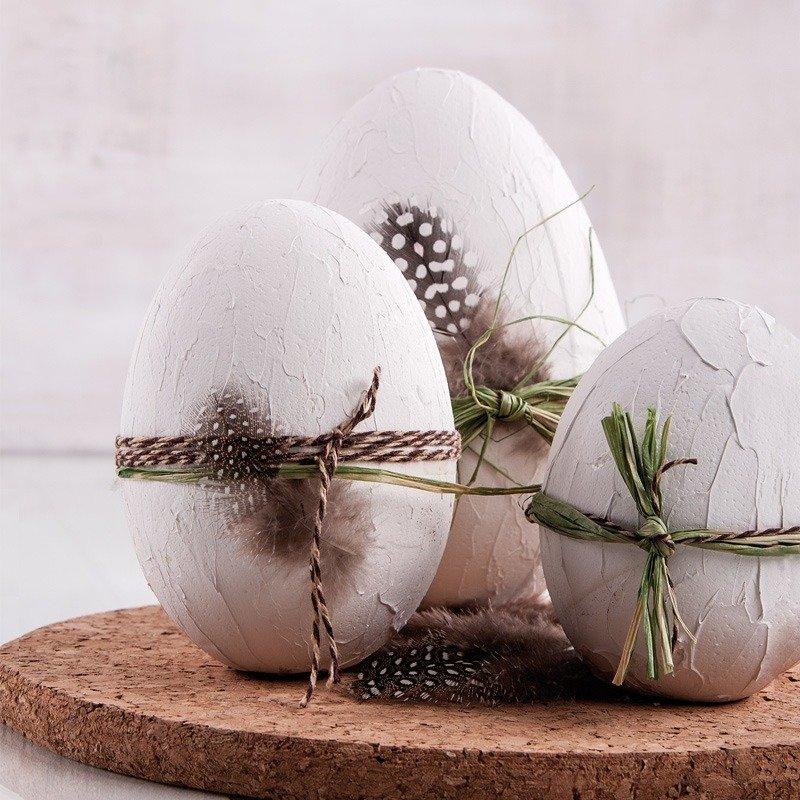 3 Ostereier mit weißer Spachtelcreme.