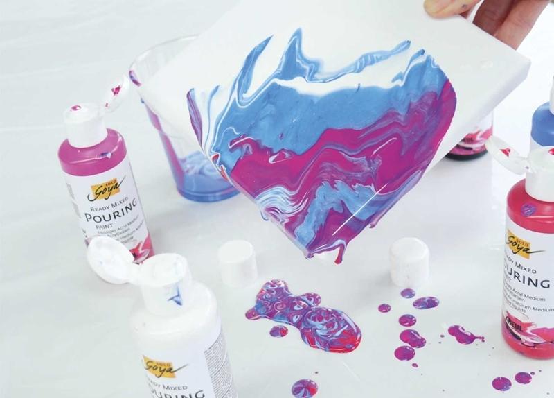 Flüssige Pouringfarbe wird auf einem Keilrahmen verteilt.