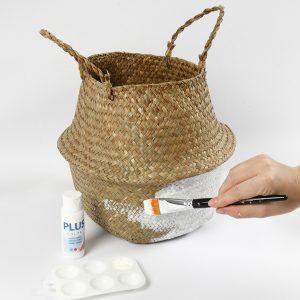 Weiße Farbe wird auf einen Seegraskorb aufgetragen.