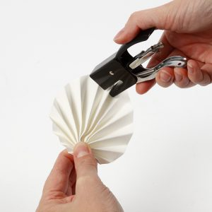 Ein gefaltetes Blatt aus Lederpapier wird zusammengeheftet.