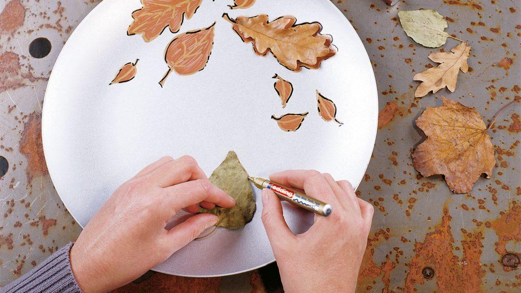 Ein Buchenblatt wird als Vorlage auf einem Teller umzeichnet.