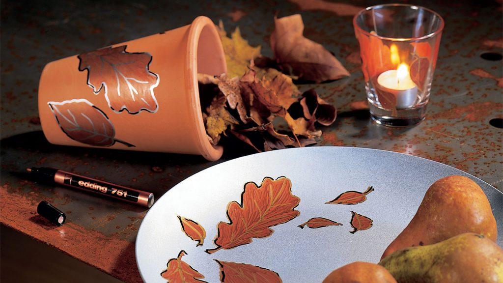 Ein Blumentopf, ein Teller und ein Glas mit aufgemalten Herbstblättern.