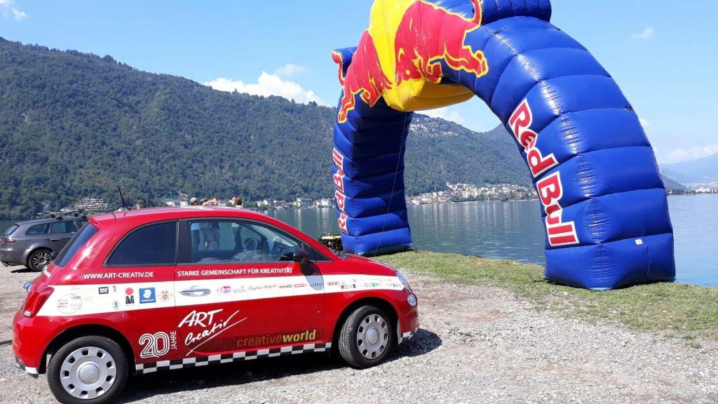 Roter Fiat vor einem Luftbogen von Red Bull.