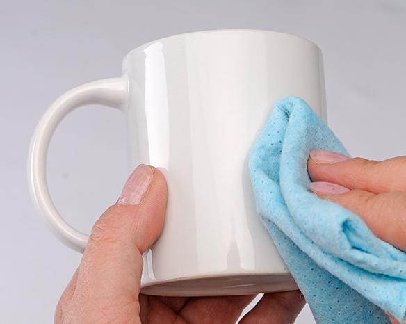 Ein weißer Becher wird mit einem Tuch gesäubert.