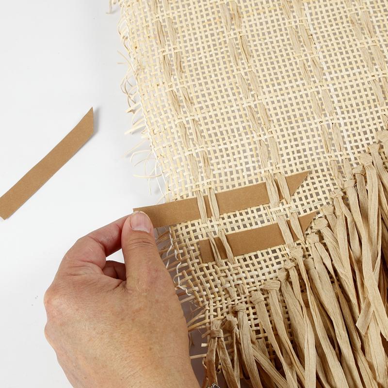 Streifen aus Kunstlederpapier werden durch das Rattan von der Wanddeko geschoben