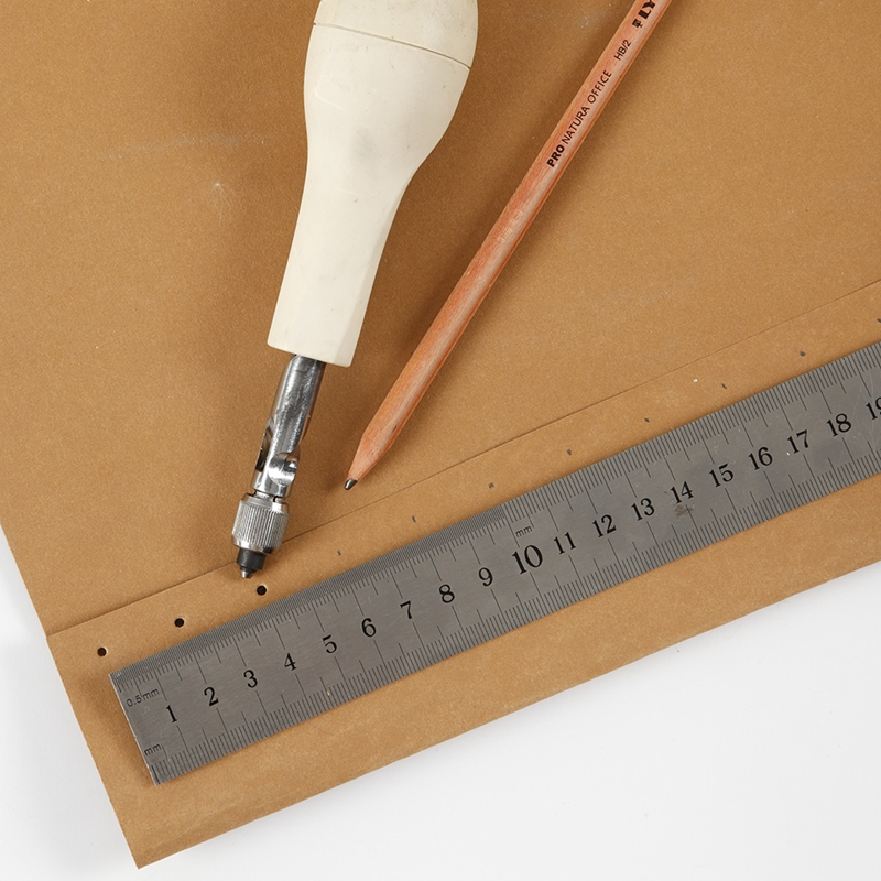 Löcher werden in Kunstlederpapier gestanzt