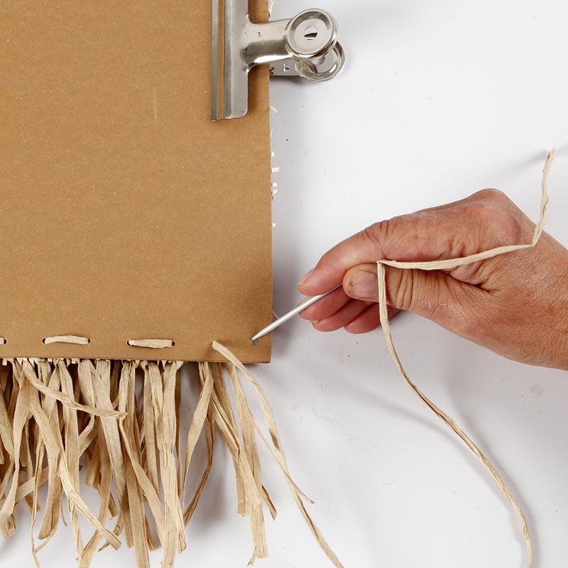 Eine Wanddeko aus Kunstlederpapier wird mit Bast zusammengenäht