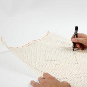 Ein Muster wird auf das Knüpfgewebe gezeichnet