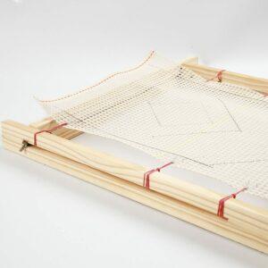Das Knüpfgewebe wird in einen Rahmen gespannt