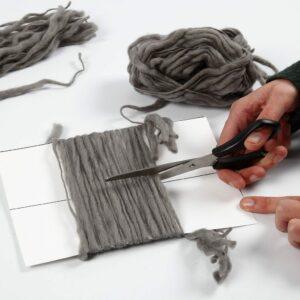 Wolle wird in kurze Abschnitte für Wandbehänge geschnitten