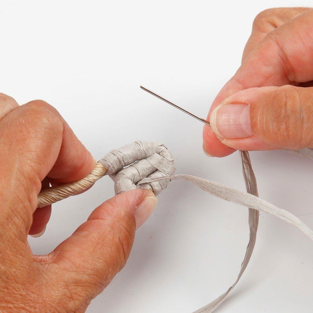 Eine Maisschnur wird mit Papierbast für einen Korb umwickelt