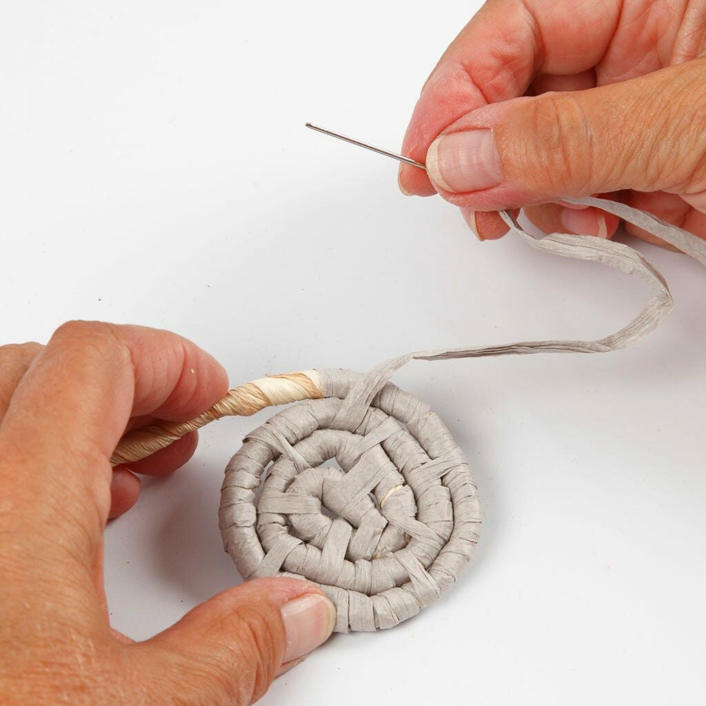 Eine Maisschnur wird mit Papierbast zu einer Spirale geformt