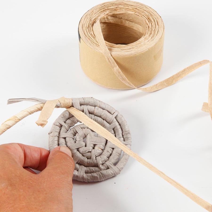 Eine zweite Farbe Papierbast wird für den Korb angesetzt