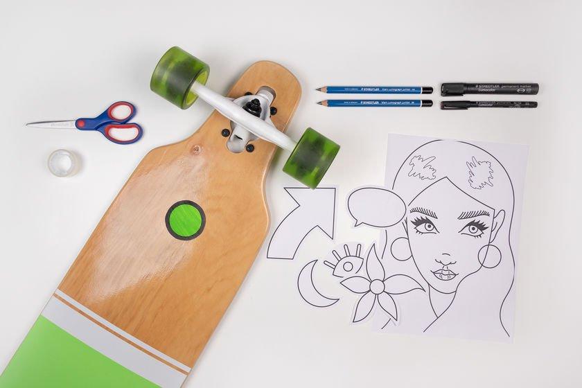 Ein Longboard, Stifte, Schere und Vorlagebogen