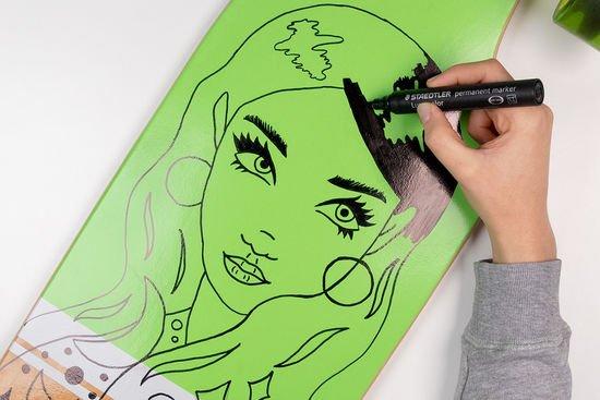 Ein Longboard wird mit einem Frauen-Motiv bemalt