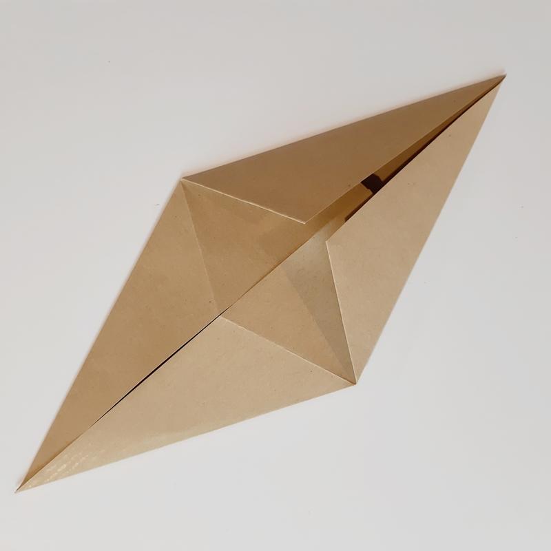 Bogen quadratisches Papier wird zu den Seiten umgefaltet
