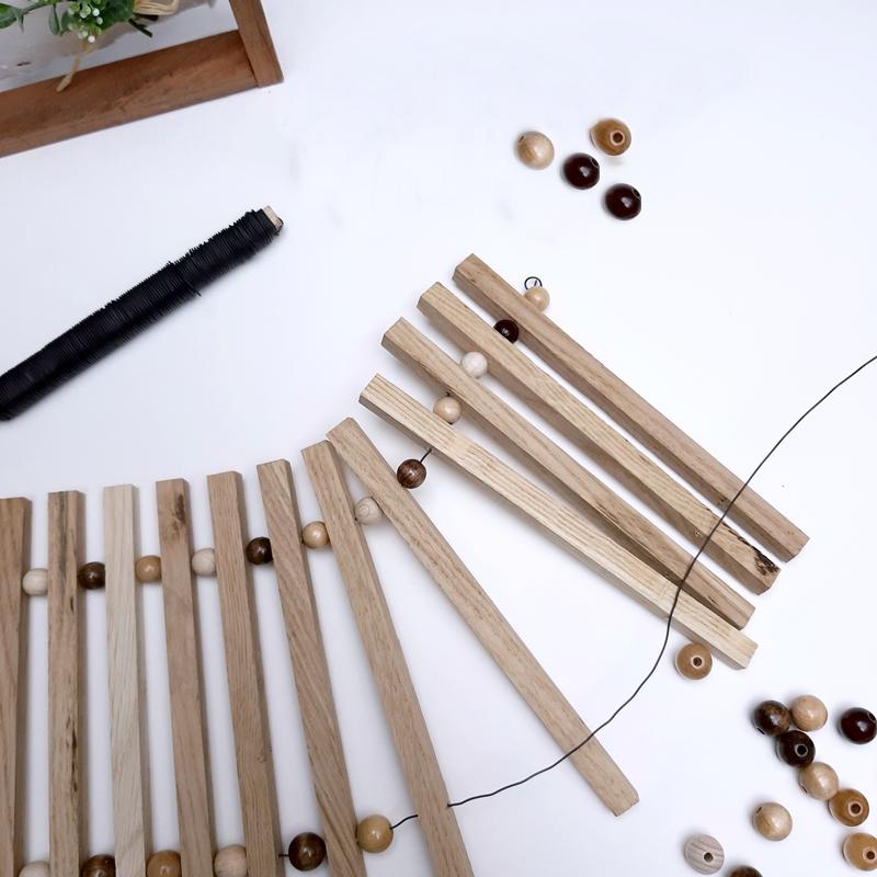 Bastelklötzchen werden mittels Perlen und Draht zusammen gebunden